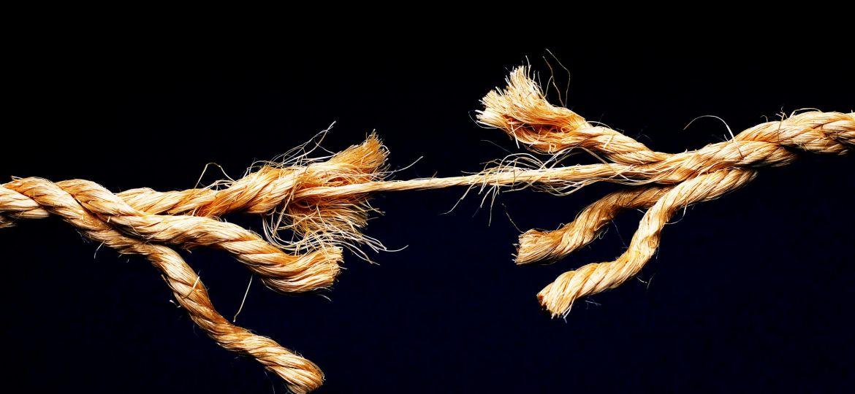 Image of fraying rope against black background