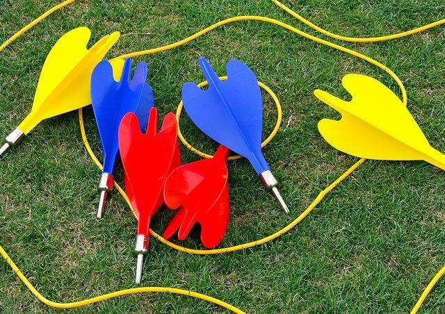 Red, blue and yellow darts in yellow circles on grass