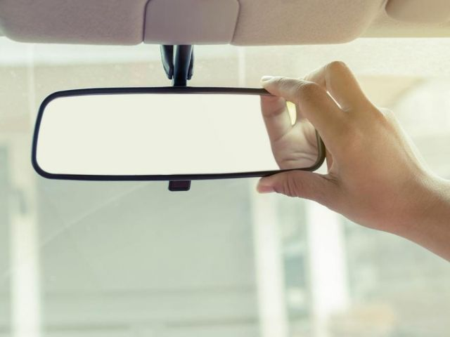Hand adjusting car rearview mirror
