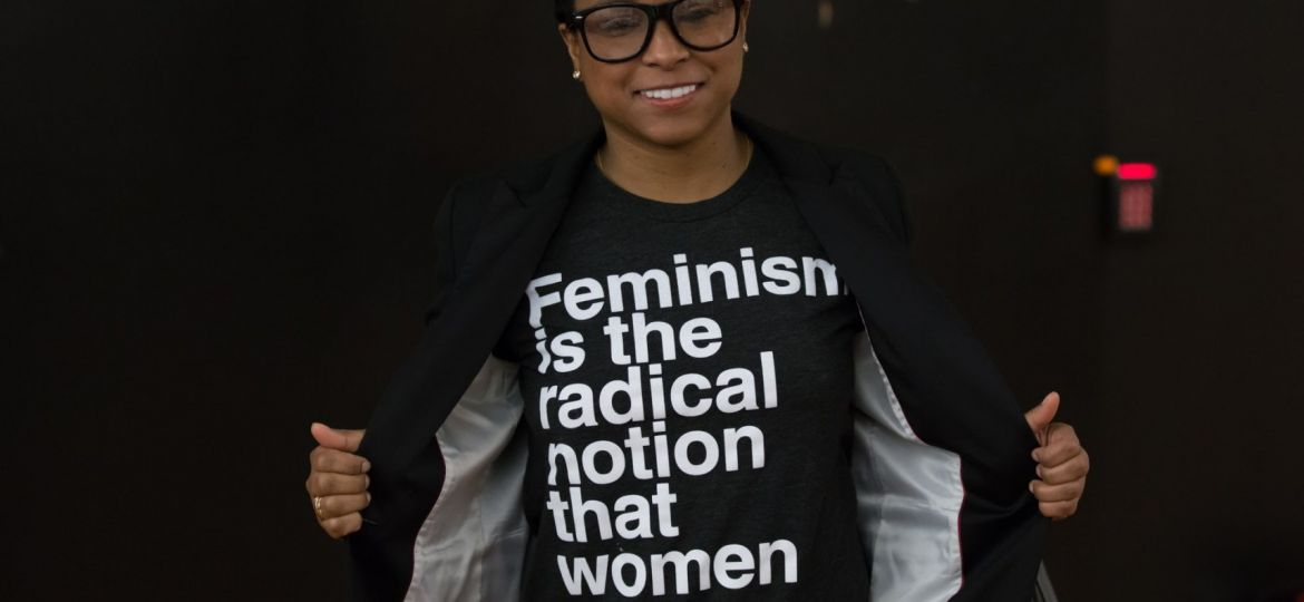 """Image of person wearing a T-shirt that says """"Feminism is the radical notion that women are people."""""""