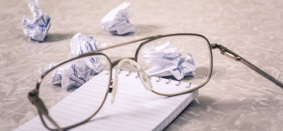 Glasses on top of notepad with wadded up papers