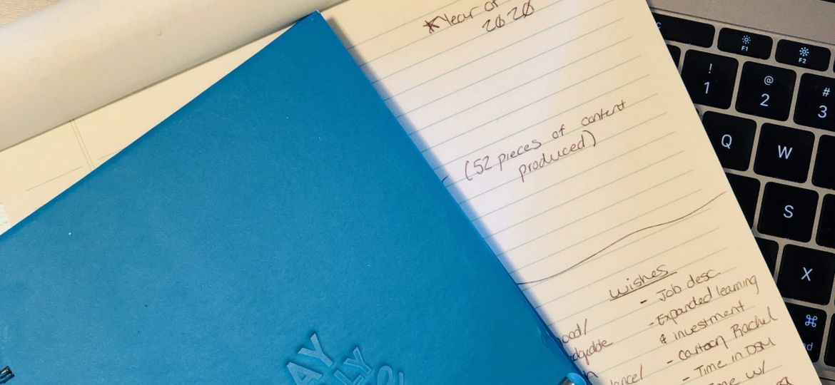Blue Play Fully Brave notebook on top of notepad and laptop