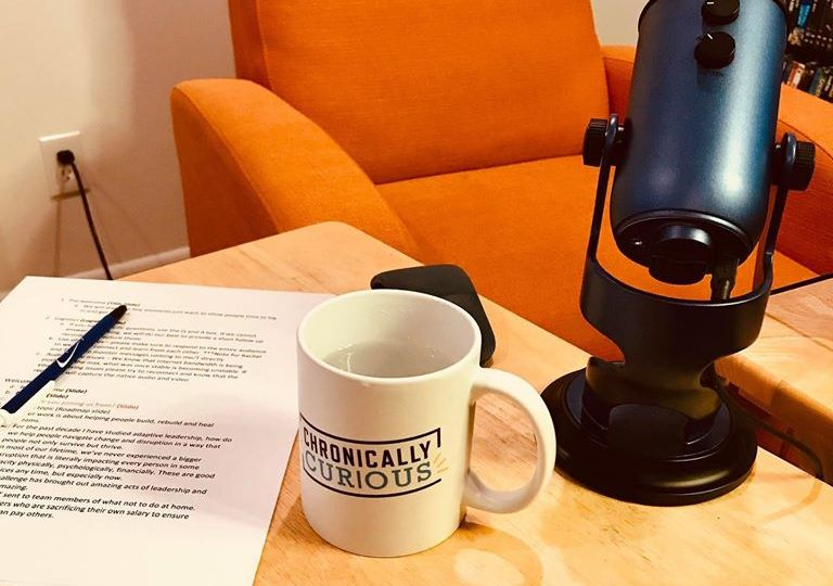 Image of Chronically Curious mug on a table next to a podcasting microphone