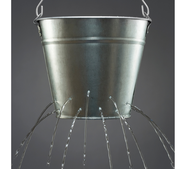 Silver bucket with holes in it spilling out water