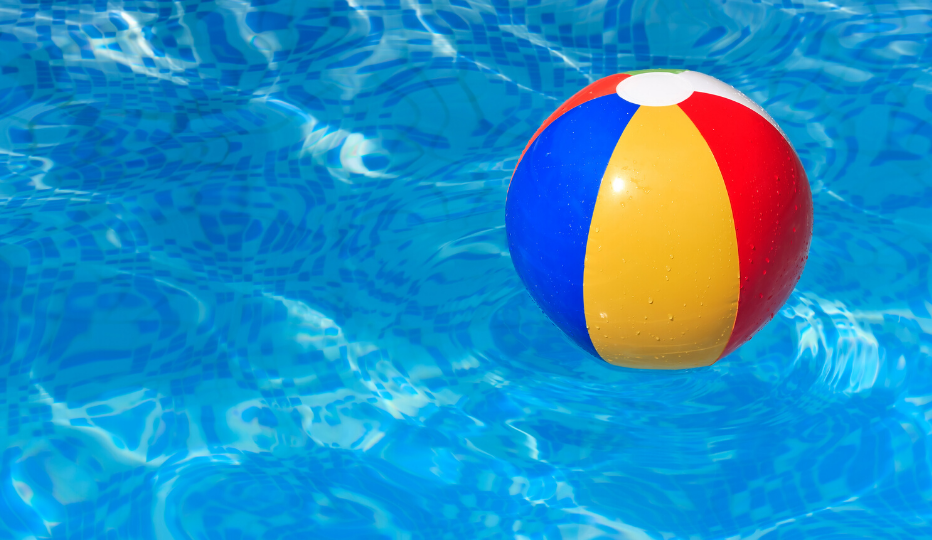 Blue, yellow and red beach ball floating in a pool