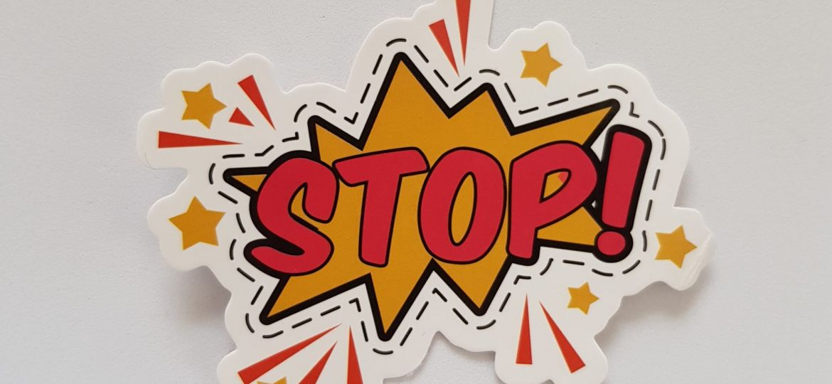 """Yellow and red sticker that says """"Stop!"""""""