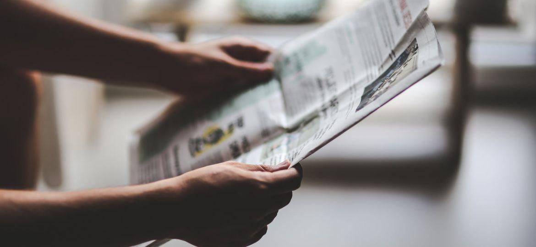 Hands holding newspaper