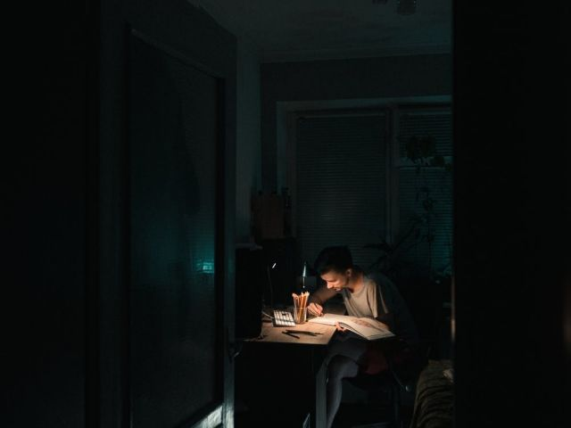 Person sitting at a desk writing in the light of a lamp