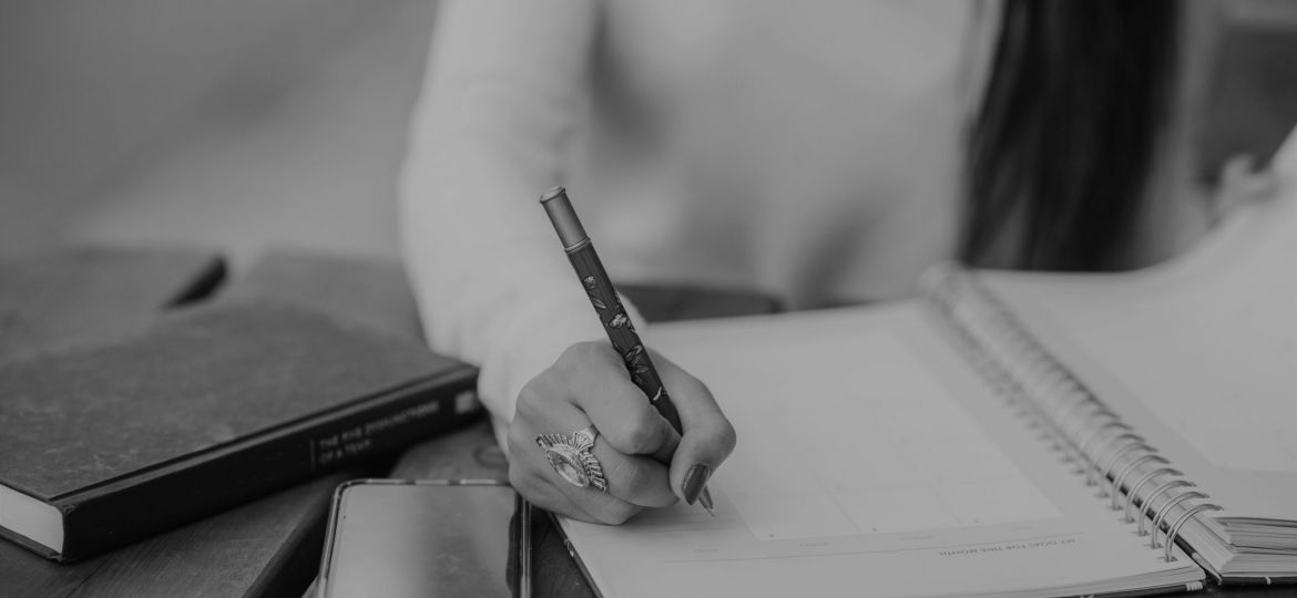 Black and white image of woman writing in a journal on a wooden table.