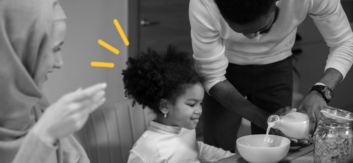 A mother, father and child sit at a table eating breakfast. The father is pouring milk into a cereal bowl for their daughter.