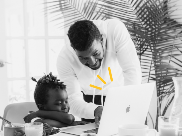 A father and son sit at a computer together eating breakfast. The father is leaning in as if helping the child with work on the computer.