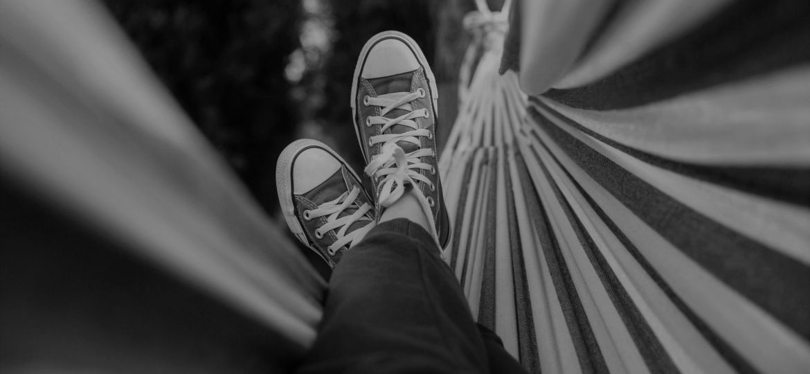 Black and white photo of person's feet in a hammock
