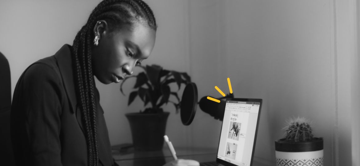 Black and white photo of a person working at a desktop next to a laptop