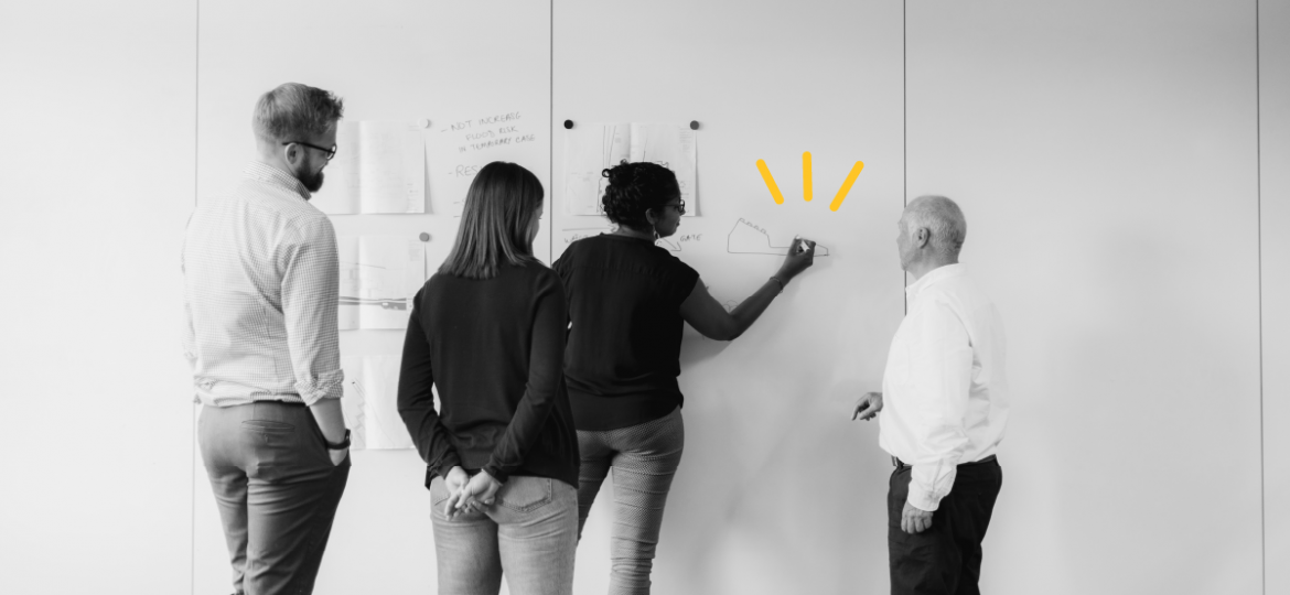 Black and white photo of a group of people writing on a white board together